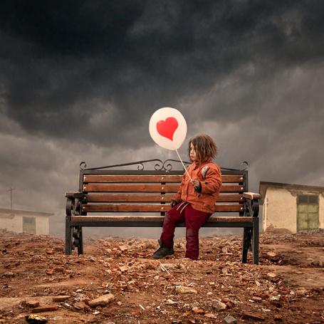 Фото Девочка сидит на скамейке на фоне домов и грозового неба и держит в руках шарик с сердечком