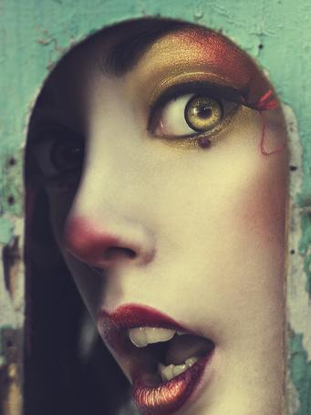 Фото Девушка с ярким макияжем смотрит, открыв рот, через маленькое отверстие в стене, фотограф Rebeca Saray / Ребека Сарай
