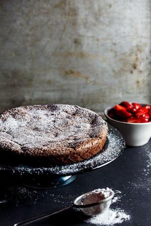 Фото Пирог присыпанный сахарной пудрой стоит на столе