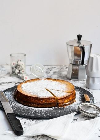 Фото Пирог с сахарной пудрой стоит на столе рядом с ножом, перечницей и мокко