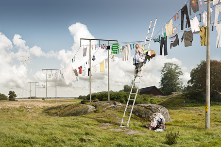 Фото Девушка вешает сушить белье на провода столбов электропередач
