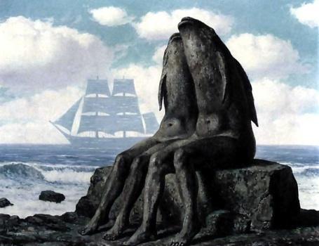 Фото Пара рыболюдей сидит на каменном выступе у берега моря, они похожи статуи, вдали виден прусник