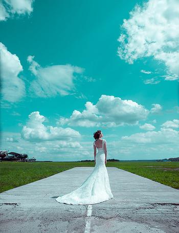 Фото Двушка, в свадебном платье стоит на дороге к нам спиной, на фоне облачного голубого неба, фотограф Владимир Зотов