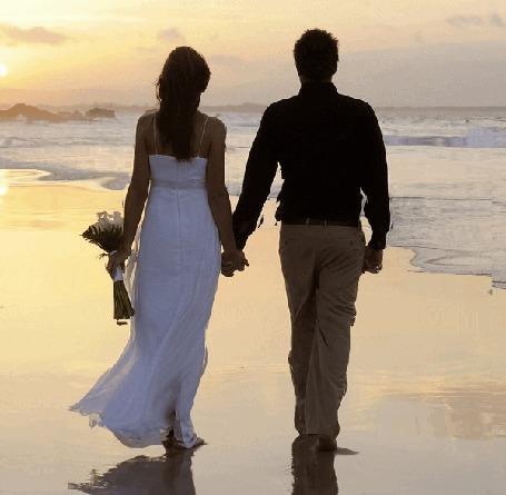 Фото Мужчина в черной рубашке и девушка в белом платье, держащая в руке букет цветов, взявшись за руки стоят в морской воде и смотрят на море