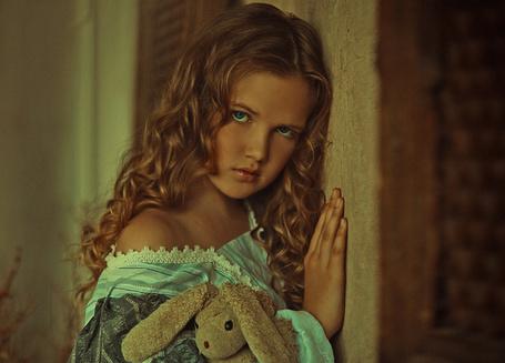 Фото Девочка с голубыми глазами, прислонилась к стене и держит мягкую игрушку зайца