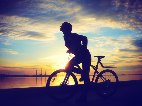 Фото Девушка на велосипеде стоит на фоне заката