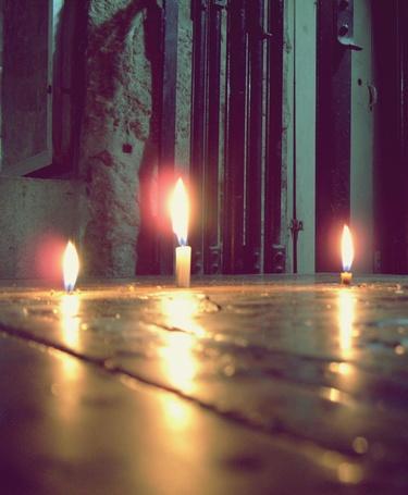 Фото Три горящие свечи на полу в подземелье