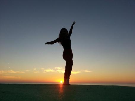Фото Девушка стоит на фоне заката