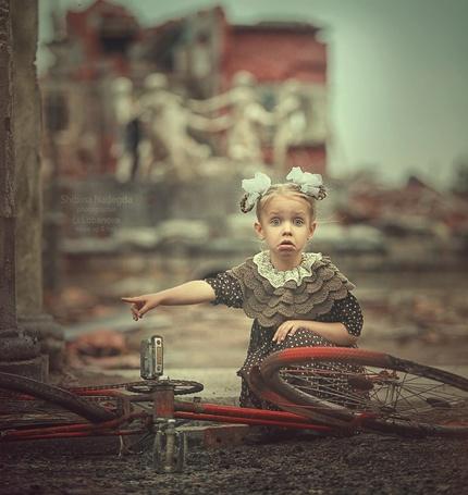 Фото Девочка сидит около велосипеда и показывает пальцем, фотограф Надежда Шибина