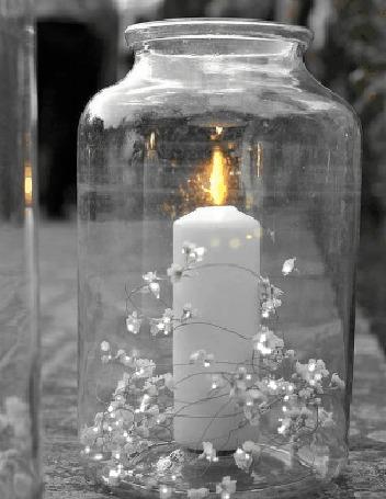 Фото Баночка с горящей свечой и цветами внутри