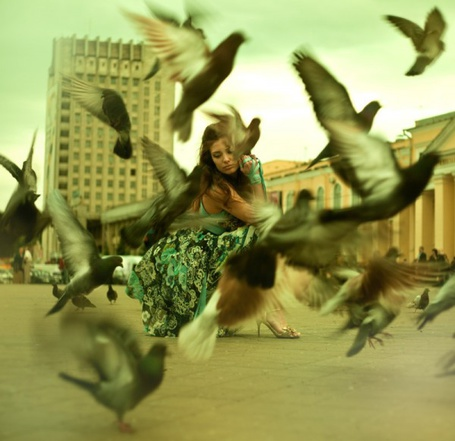 Фото Девушка, сидящая на корточках в окружении птиц, парящих вокруг нее