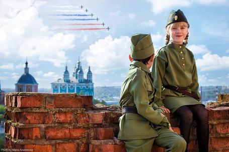Фото Дети в военной форме сидят на заборе, сзади них в небе самолеты делаю цветным дымом флаг России, фотограф Мария Аванесова