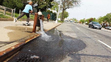 Фото Кто - то открыл на улице пожарный гидрант и вода растекается по асфальту