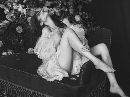 Фото Актриса Летиция Каста сидит на диване у роз