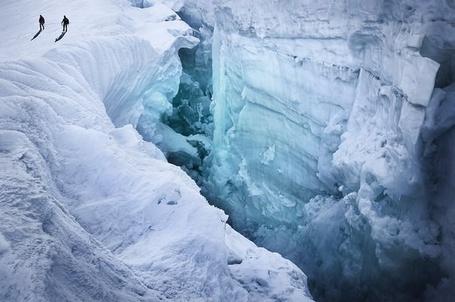 Фото Два альпиниста стоят на краю трещины во льду