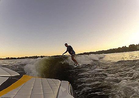 Фото Мужчина на доске для серфинга, рассекает волны исходящие от яхты