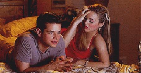 Фото Парень лежа увлеченно смотрит телевизор, а девушка в красном платье, возмущенная невниманием парня, падает с кровати