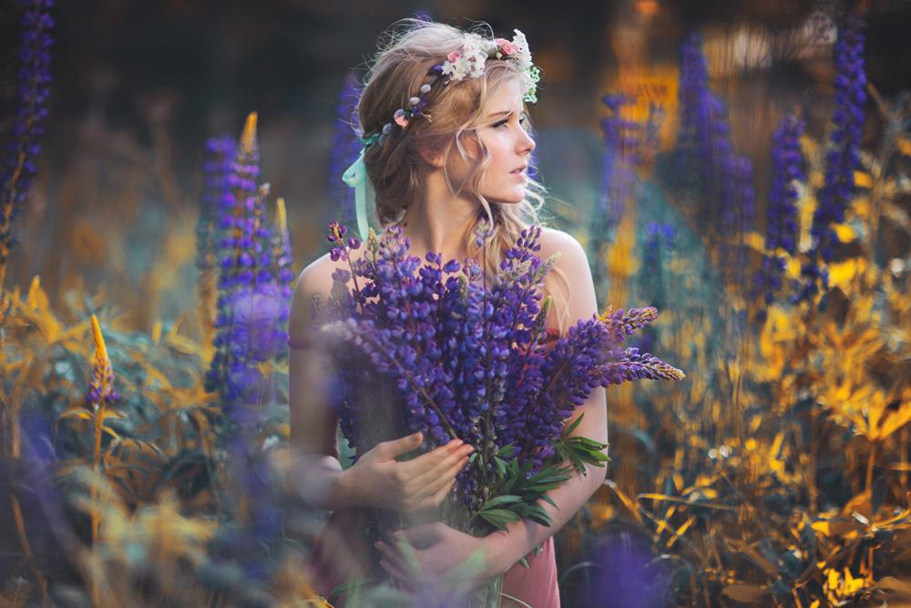 Девушка с венком на голове стоит в поле с букетом люпина в руках, автор absentii