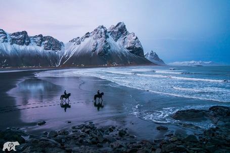 Фото Двое мужчин верхом на лошадях у берега моря на фоне заснеженных гор, by Chris Burkard