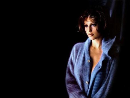 Фото Актриса и модель Laetitia Casta / Летиция Каста в голубой теплой кофте на черном фоне