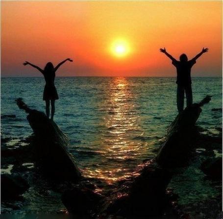 Фото Мужчина и женщина на берегу моря, на фоне заката