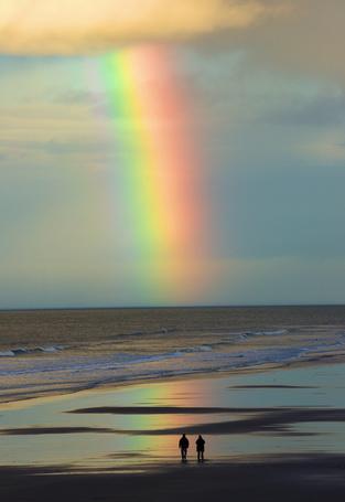 Фото Два человека наблюдают за радугой над морем