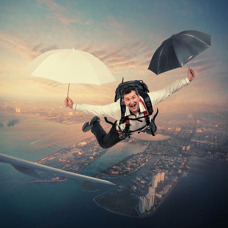 Фото Радостный мужчина парит над землей в воздухе, держа в руках белый и черный зонтики, автор Garas Ionut