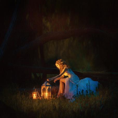 Фото Рыжеволосая девушка, сидящая на стволе поваленного дерева, держит рукой декоративный фонарь с горящей в нем свечой, рядом стоит фонарь меньших размеров