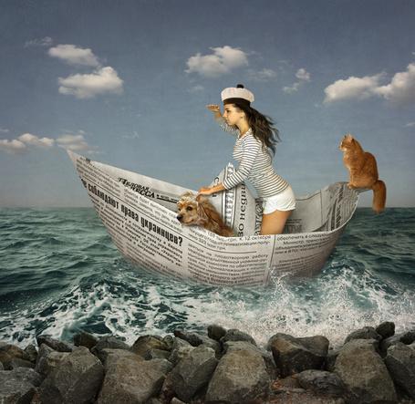 Фото Темноволосая девушка в матросской шапке и тельняшке, стоящая в лодке, сделанной из газеты, плывущей возле каменистого берега вместе с рыжим котом и собакой, автор Ирина Кузнецова