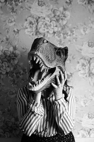 Фото Девушка держит перед своей головой голову динозавра