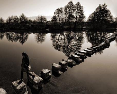 Фото Девушка переходит реку по каменным сваям