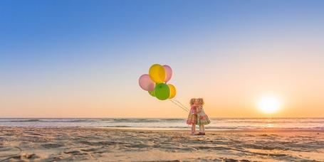 Фото Две девочки, у одной из которых воздушные шарики в руке, обнимаются на берегу моря на закате