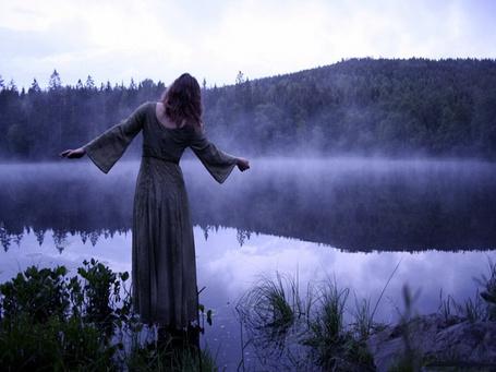 Фото Стройная девушка в длинном платье, стоящая у берега горного озера на рассвете, на фоне легкого туманного испарения от водной поверхности