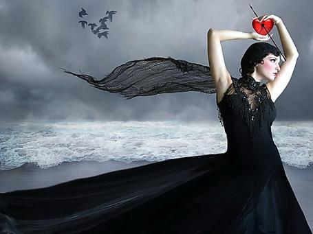 Фото Черноволосая девушка в длинном, черном платье, стоящая на берегу бушующего моря держит над головой красное сердечко, пронзенное стрелой из лука