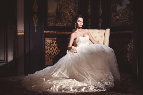 Фото Шикарная девушка на классическом кресле в свадебном платье