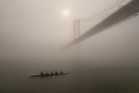 Фото Утренняя тренировка гребцов на байдарке по морскому заливу с уходящим в густую, туманную даль мостом на фоне утреннего небосклона с едва видневшимся солнечным диском, автор Татьяна Гориловская
