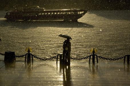 Фото Влюбленная пара стоит на набережной под дождем, by Photoleto