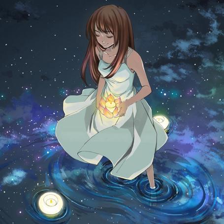 Фото Девушка держит свечу, стоя в воде, в которой отражается звездное небо