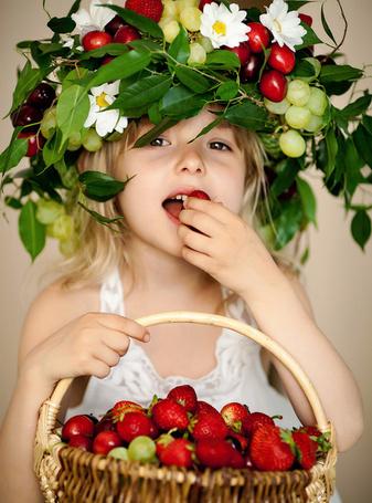 Фото Девочка с красивым венком на голове, сделанный из ягод, цветов и листьев, держит в руке плетенную корзину с клубникой
