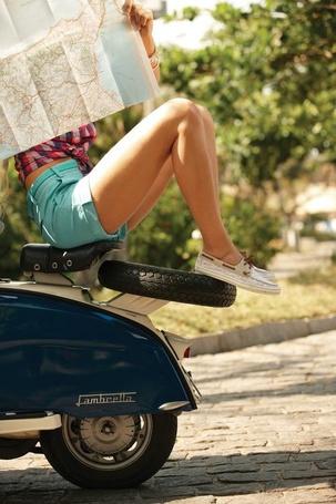 Фото Девушка сидит на мотоцикле подняв ноги и смотрит на карту