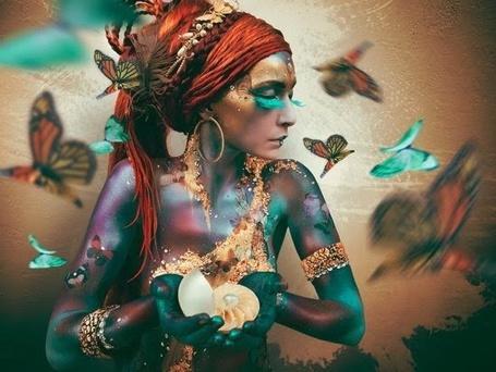 Фото Экзотически одетая девушка, тело которой окрашено под бронзу, в браслетах и в красном платке на голове, держит в руках жемчужную раковину, вокруг летают разноцветные бабочки