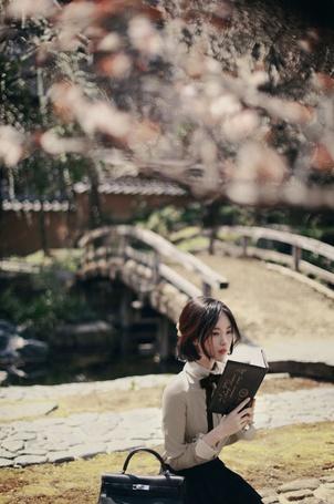 Фото Девушка - азиатка сидит на камнях и держит в руках книгу. На ее фоне мост и здание с черепичной крышей