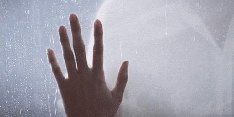 Фото Девушка и парень прикасаются ладонями через стекло