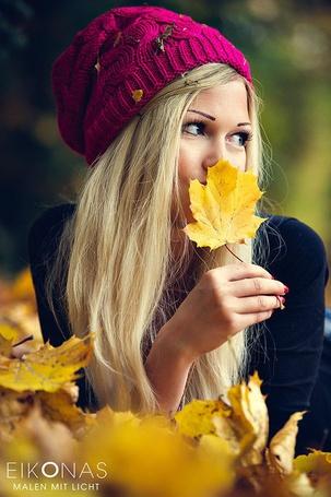 Фото Блондинка в шапочке держит в руке кленовый листок