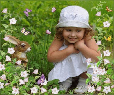 Фото Маленькая девочка, в белой шапочке и сарафанчике, сидит в саду, среди цветов, рядом с ней игрушечная белка