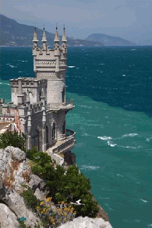 Фото Замок Ласточкино гнездо стоит на высокой горе у моря, над ним кружатся чайки
