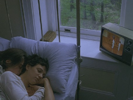 Фото Девушка с парнем сладко спят, а по телевизору, который стоит на подоконнике, показывают карате, за окном видны деревья