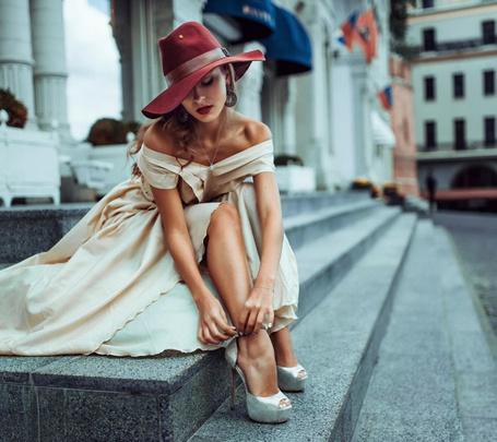 Фото Девушка в шляпке застегивает туфли, сидя на ступеньках