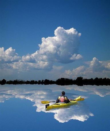 Фото Спортсмен в лодке плывет по водной глади, отражающей небо, работа автора по имени Peter Holme III