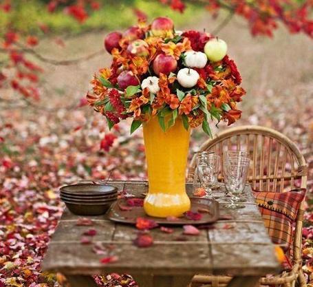 Фото Букет из осенних цветов, листьев и спелых яблок стоит на столе на природе, посреди опавшей листвы